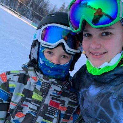 Two young boys in colorful ski gear smiling
