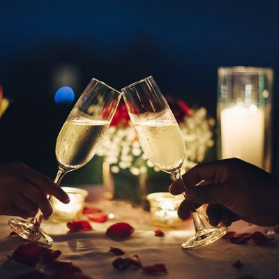 Two champagne glasses toasting with candles and roses on the table