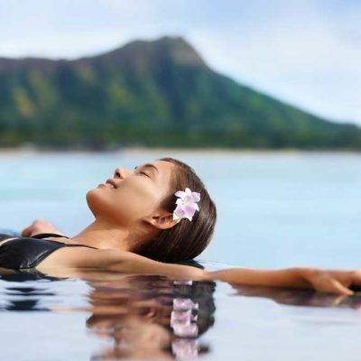 women with pink flower in her hair lying back in the water