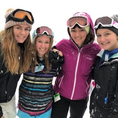 4 smiling young ladies in ski gear