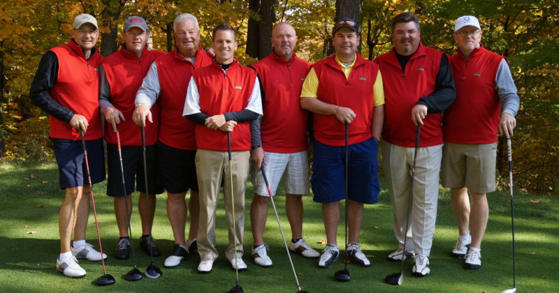 A group of golfers in red uniforms enjoys a tournament at Treetops Resort