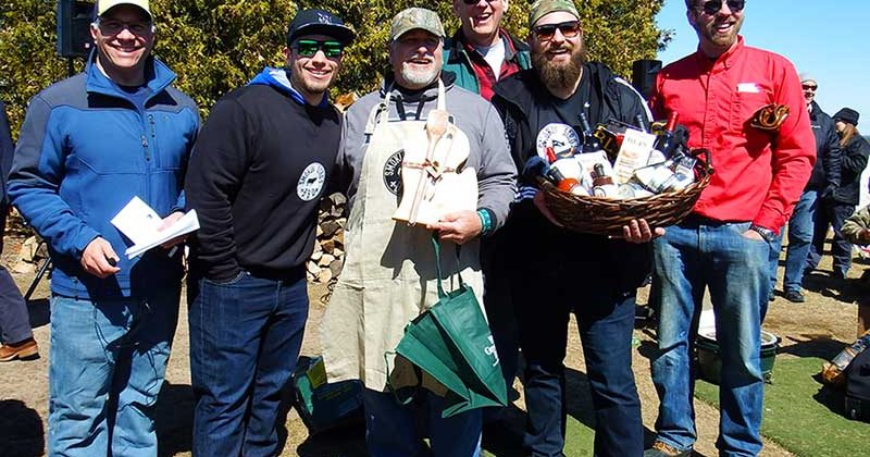 5 men outdoors smiling, one wearing an apron and one holding a gift basket