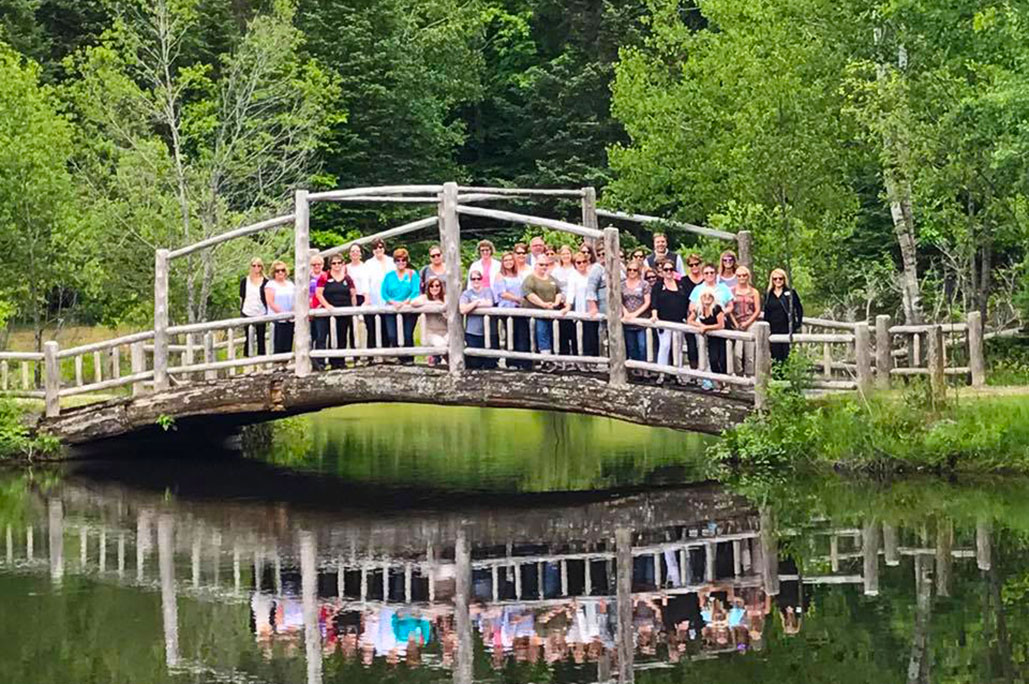 large group of professionals standing on wooden bridge