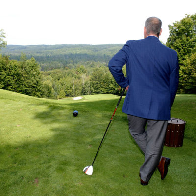 Man in blue sport coat holding a golf club for a Treetops Business Lunch