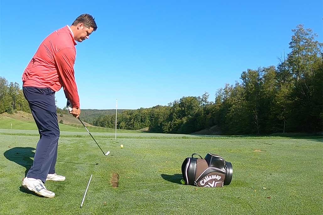 Tall man in read shirt getting ready to swing a golf club