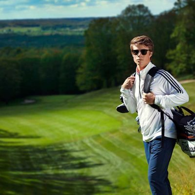 Junior golfer carrying bag of golf clubs standing on golf course.