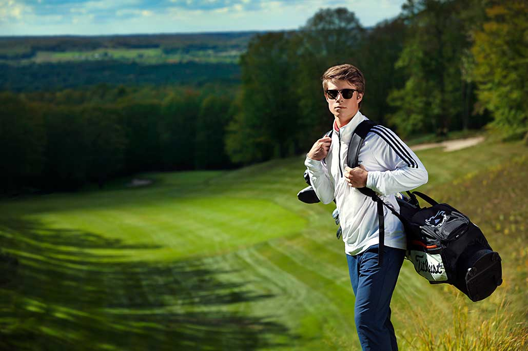 junior golfer carrying bag og golf clubs standing on golf course