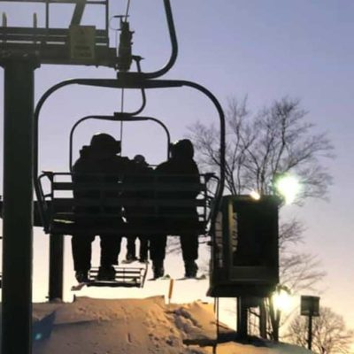 skiers on a chairlift at sunset