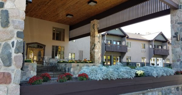 The Treetops Lodge main entry with landscaping in the foreground.
