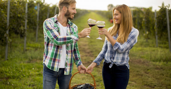 A man and a woman in flannel shirts hold a basket of grapes, each person holds a glass of red wine