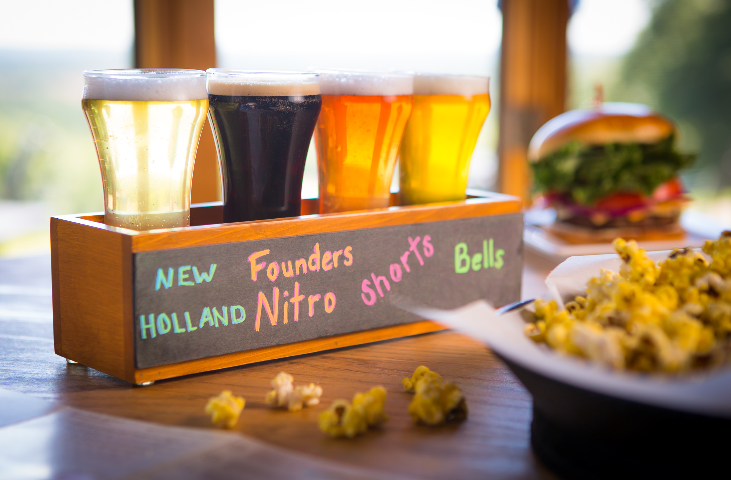 a flight of four beers lined up with a basket of popcorn in the foreground