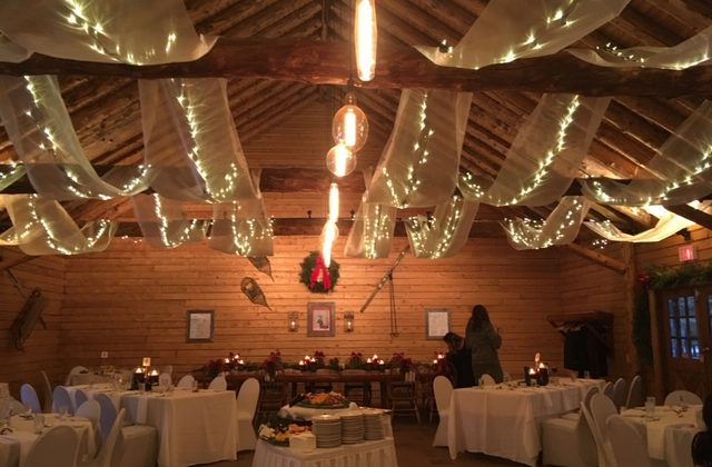 a holiday party space decorated for a large Christmas party with string lights, white tablecloths, garland and wreath