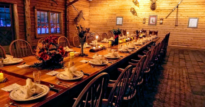 long wooden table set for elegant dinner in cozy cabin setting