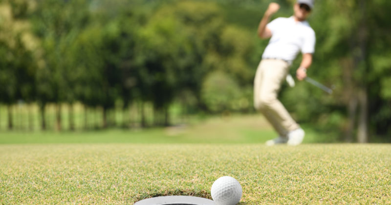 Golf ball rests next to hole as man in background reacts