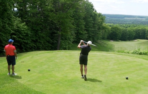 Male golfer teeing off with friend looking on