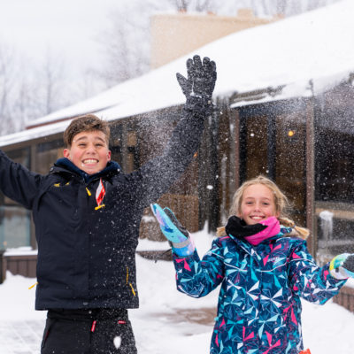 young boy and girl throwing snow in air