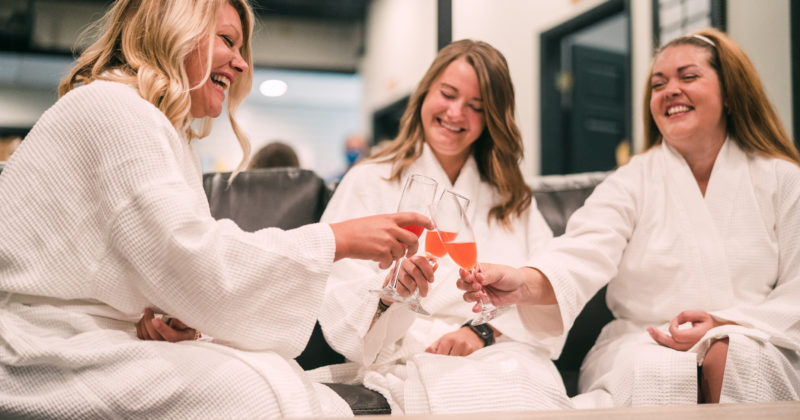 Three women smiling and toasting in spa