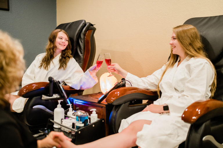 Two young women toasting a mimosa while enjoying spa pedicure