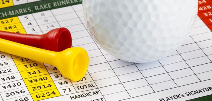 A white golf ball and yellow and red tees lay on top of a golf scorecard.