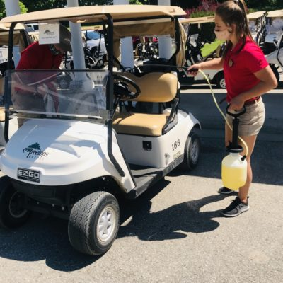 Two employees sanitize a golf cart at Treetops Resort.
