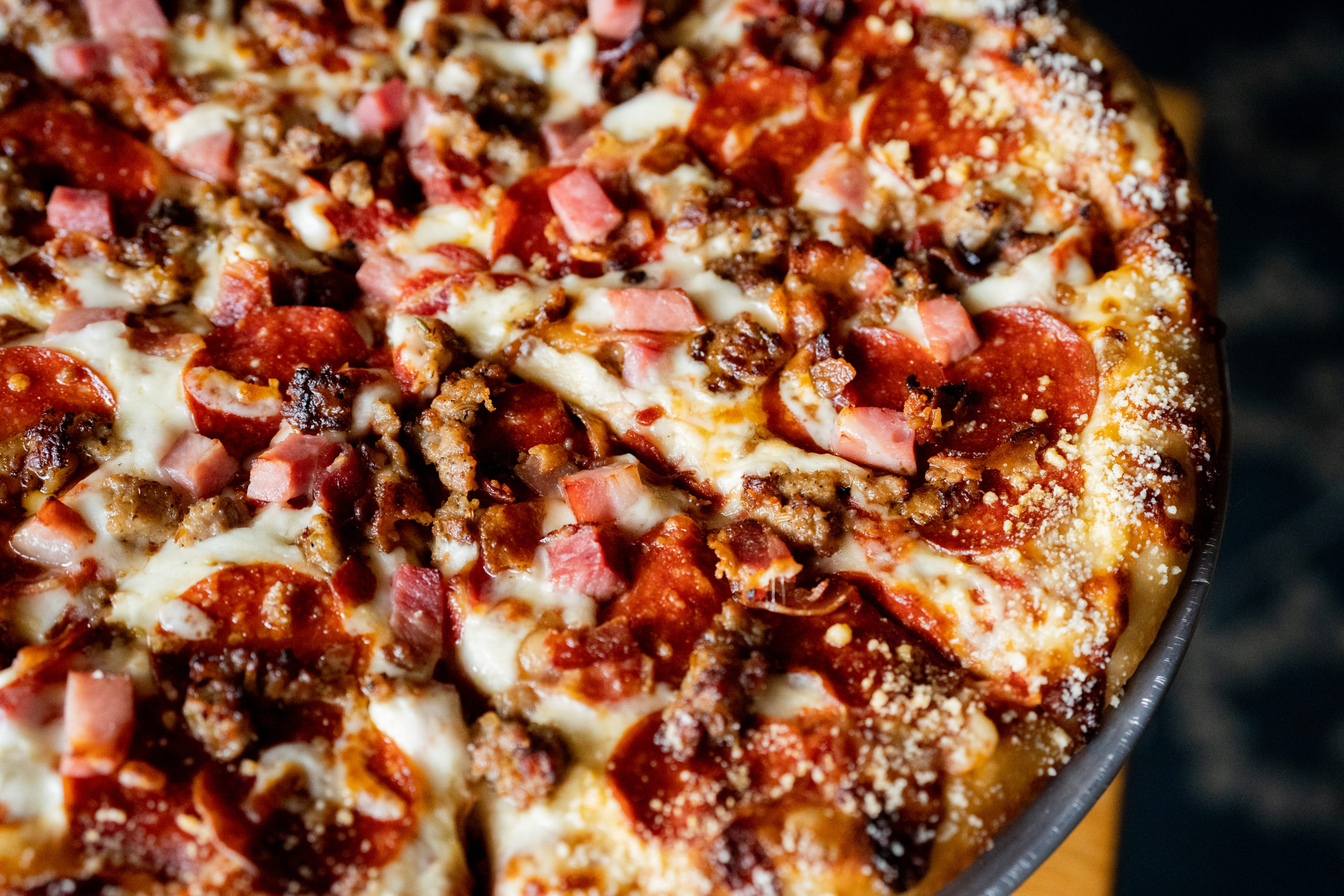 A freshly baked meat lover's pizza with pepperoni, sausage, and ham at Treetops Resort.