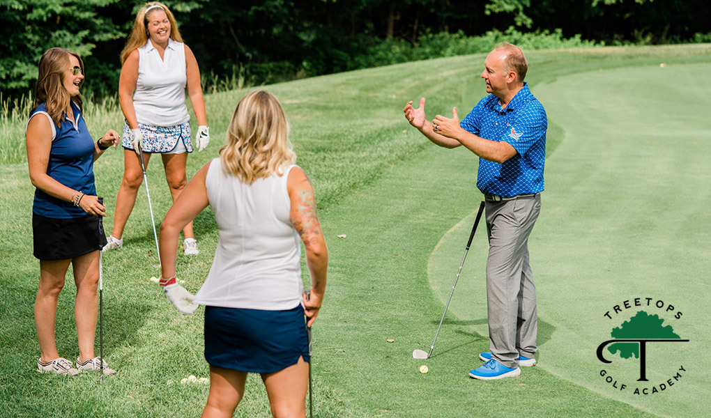 A golf instructor provides a golf lesson to three students, with the Treetops Golf Academy logo in the bottom right corner.
